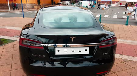 por que : Menton, France - March 3, 2018: Black Tesla S Model (Rear View) Electric Car Park on a Square in Menton on The French Riviera. The Tesla Model is a Luxury Full-Sized Electric Five Door - 4K Video