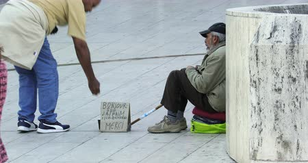 bezrobocie : Paris, France - October 16, 2018: Homeless Man Begging In Paris Streets, A Man Is Giving Money. District Defense, Europe - DCi 4K Resolution Wideo