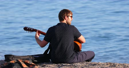 kytarista : Menton, France - December 4, 2018: Young Man Playing An Acoustic Guitar On The Beach, Mediterranean Sea, French Riviera, Europe - DCi 4K Resolution