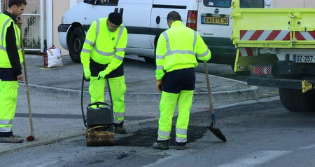 pression : Roquebrune-Cap-Martin, France - December 5, 2018: Workmen Repairing Road Surface Damaged By Weather And Traffic, Industry And Teamwork - DCi 4K Video