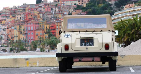 volkswagen : Menton, France - December 7, 2018: Vintage Volkswagen Thing 1973 (Rear View) Car On The Beach With Colorful Houses Of Menton Old Town In The Background, Mediterranean Sea, French Riviera, Europe - DCi 4K Resolution Stock Footage