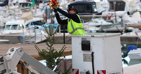 pleasure boats : Menton, France - December 7, 2018: Worker On The Crane Install And Decorate The Christmas Tree, Decoration Of A Large Christmas Tree With The Port Of Menton In The Background, French Riviera, Europe - DCi 4K Resolution