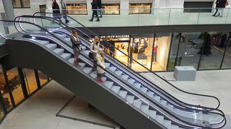 Lyon, France - January 4, 2019: Three Women Standing On Going Down Escalator At A Shopping Center In Lyon, France, Europe - 4K Resolution