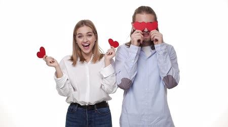 csatlakozott : Slow-motion Young couple together playing paper hearts in casual smart cloths. Stock mozgókép