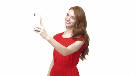 facetime : Beautiful teen girl making video call using her mobile phone. Young teenage girl talking to friends online, video chatting, blogging, waving hand, laughing. Stock Footage