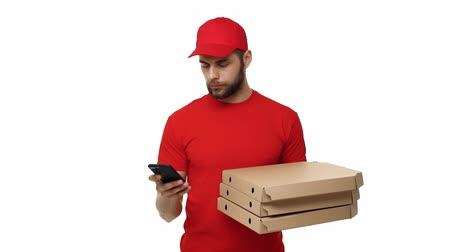 ekspres : Delivery boy in a red uniform holding a stack of pizza boxes and checking order on mobile phone. Isolated over white background.