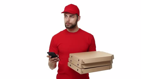listonosz : Delivery boy in a red uniform holding a stack of pizza boxes and checking order on mobile phone. Isolated over white background.
