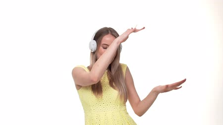 bas : Excited woman in headphones listening to the music, slow motion, isolated on white studio background.