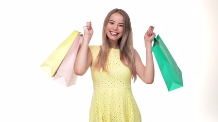 шопоголика : Happy young woman shopper holding shopping bags on white background in studio. Стоковые видеозаписи