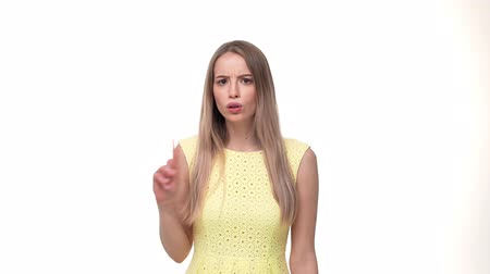 odmítnutí : Young serious woman standing isolated over yellow background while looking camera says no