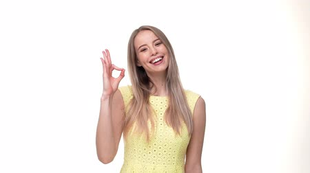 договориться : Young excited woman showing ok with fingers over gray background.