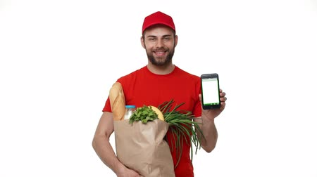 provést : Handsome delivery man showing mobile phone on white background