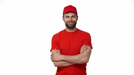 listonosz : handsome male service industry worker deliveryman in uniform posing on white background with arms crossed confidence professionalism career employment concept. Wideo