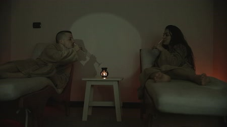 querido : Couple in a bathrobe lying on bed at spa wineglasses at the spa center Stock Footage