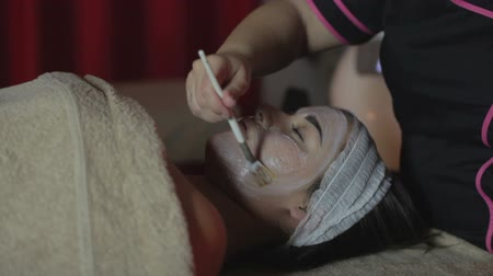 amado : Young woman relaxing under the gentle touch of the specialist applying her cheeks white facial mask with rejuvenating effects