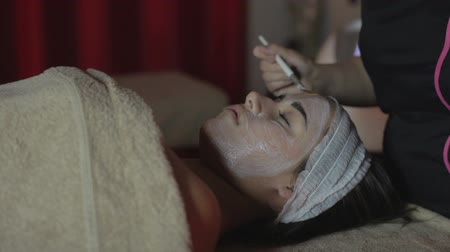 acalmar : Young woman relaxing under the gentle touch of the specialist applying her cheeks white facial mask with rejuvenating effects