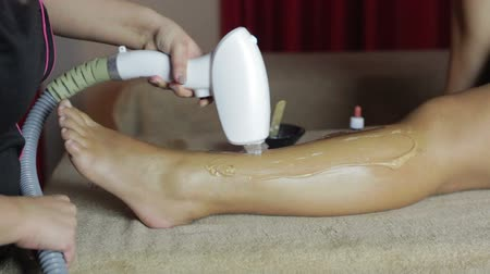 calming down : Close-up of woman receiving epilation laser treatment on leg