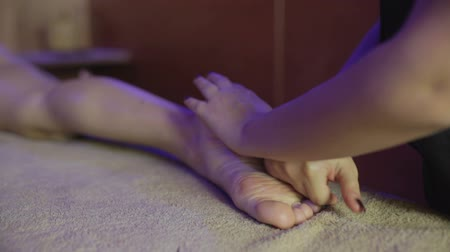 lefekvés : Massage of young woman in spa salon. Working hands masseuse
