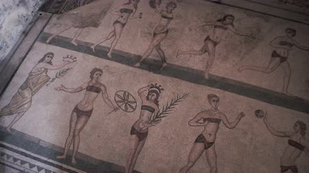 купальник : PIAZZA ARMERINA, ITALY - APRIL, 24: The bikini mosaic, showing women playing sports. Roman Villa del Casale, large and elaborate Roman villa designated as a UNESCO World Heritage Site, famous for the extraordinary collection of frescoes and mosaics on A Стоковые видеозаписи