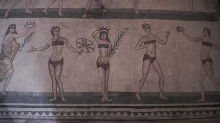 dünya mirası : PIAZZA ARMERINA, ITALY - APRIL, 24: The bikini mosaic, showing women playing sports. Roman Villa del Casale, large and elaborate Roman villa designated as a UNESCO World Heritage Site, famous for the extraordinary collection of frescoes and mosaics on A Stok Video