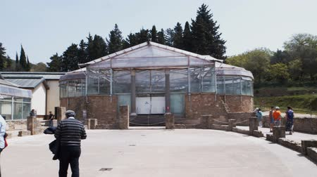nyaraló : PIAZZA ARMERINA, ITALY - APRIL, 24: Tourists visiting Roman Villa del Casale, Roman villa designated as a UNESCO World Heritage, famous for the extraordinary collection of frescoes and mosaics on April 24, 2019 Stock mozgókép