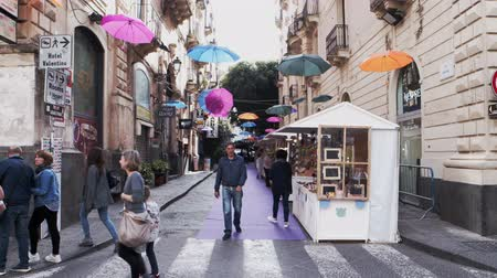 turistik : CATANIA, ITALY - APRIL, 26: View of colorful umbrellas hanging in the wires of the balconies on April 26, 2019 Stok Video