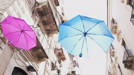 CATANIA, ITALY - APRIL, 26: View of colorful umbrellas hanging in the wires of the balconies on April 26, 2019 Stock Footage
