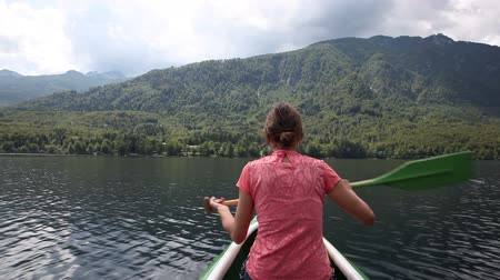 kürek çekme : Woman exploring lake Bohinj canoeing on a wooden canoe during the summer season, Slovenia