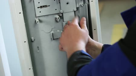 strongbox : The worker a figured key twists a nut in the locking mechanism of the safe. Close up. Close up. All accessories and key of metal color. In a shot the locking plug of the safe is visible. Stock Footage