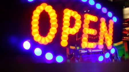entrance : Glowing open neon display sign in a window rack focus