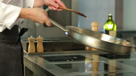 prepare food : The chef cooks on the skillet potatoes with onion. With olive oil. Garnish. Fresh food. Useful food. The chef in the kitchen. Frying plate. Write cooking in the restaurant. Oil in the background. Stock Footage