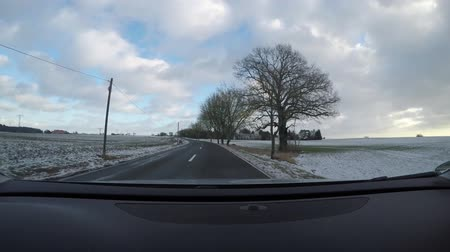 POV shot of a car driving on a winter asphalt road in snowy landscape