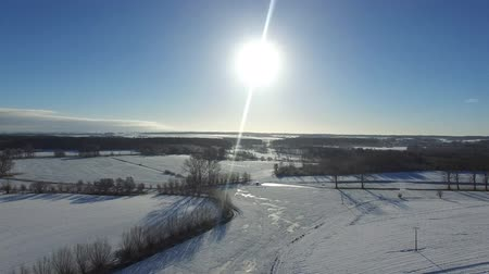 aerial view  fly over beautiful snowy landscape with sun and blue sky in germany - dronen flight