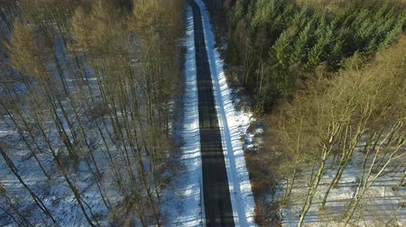 aerial view fly over road in snowy winter forest landscape - dronen flight
