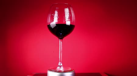 gif : Red wine in glass on colorful background