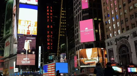 apple sign : New York City, USA advertising billboards at Times Square. Night view of Times Square neon lights including Ernst & Young illuminated sign and US Armed Forces recruiting station. Stock Footage