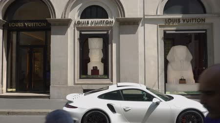 car designer : Milan, Italy Via Monte Napoleone fashion district with luxury car. Day view of people window shopping outside famous Milano street designer boutique shop Louis Vuitton. Stock Footage