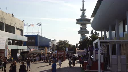 yunan : Thessaloniki, Greece visitors inside International annual fair grounds. Crowd walking outside pavilions with OTE Telecommunications Tower background view.