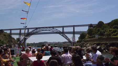 john : Porto, Portugal day view of tourists aboard a ship on Douro river, before iconic bridge. Unidentified crowd on a sailing tourist ship with view of Maria Pia and St John bridges. Stock Footage