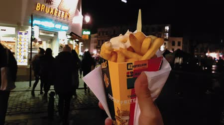 batatas fritas : Hand holding a cone of Belgian fries spilled with sauce. Night view of frites portion served with mayonnaise in Brussels. Stock Footage