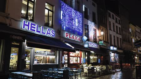 фасады : Brussels, Belgium Greek fast food restaurants, close to Grand Place. Night view of comfort food restaurants with outdoor seating & Hellenic region names as Hellas, Plaka and Mykonos.