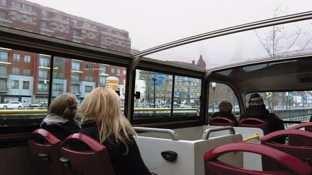 see off : Brussels, Belgium city Sightseeing Hop-On Hop-Off service bus. Cloudy day canal view of unidentified tourists on double decker bus with glass rooftop.