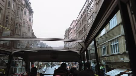 sight seeing : Brussels, Belgium city Sightseeing Hop-On Hop-Off service bus. Cloudy day city view of unidentified tourists on double decker bus with glass rooftop.