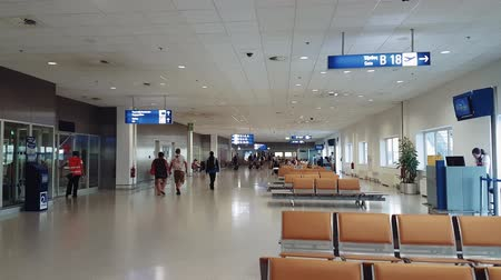yunan : Athens, Greece airport gates waiting area with passengers. Unidentified people at gatehouse with seating and counter, before boarding their flight at Athens International Airport Eleftherios Venizelos. Stok Video