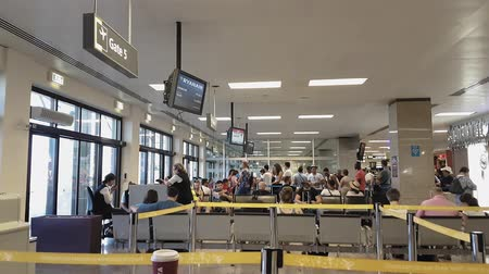 мальтийский : Malta International Airport MLA gates with passengers. Unidentified people waiting at the boarding area next to the departure gates of the Maltese airport. Стоковые видеозаписи