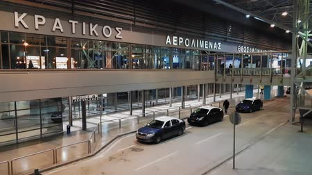 estacionado : Parked taxis at the entrance of Thessaloniki, Greece SKG airport. Night view of blue and white taxis at arrival area of International airport Makedonia, under Greek sign State Makedonia airport.