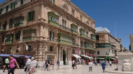 palazzo malta : Valletta, Malta pedestrian zone and traditional Maltese buildings of historic city with crowd. Day view of 1876 limestone Palazzo Ferreria at Republic Street after City Gate entrance, on a sunny day. Stock Footage