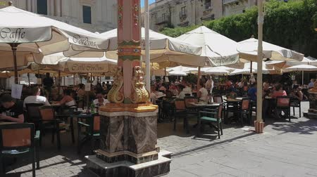 caffe : Valletta, Malta Historic Caffe Cordina outdoors seating at Republic Square. Day view of tourists at the open air tables of 1837 flagship coffee shop on Republic Street.