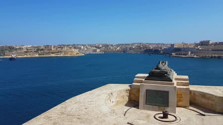 kuşatma : Valletta, Malta War Siege Memorial bronze sculpture. Day view of soldier statue lying on a catafalque next to Siege Bell War memorial, overlooking the Grand Harbour on a sunny day. Stok Video