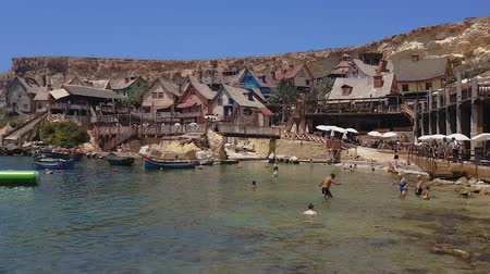travel theme : Mellieha, Malta Popeye village theme park view. Visitors bathing on the beach before wooden buildings of former Popeye 1980 musical film set, Sweethaven Village, turned to an attraction fun park. Stock Footage
